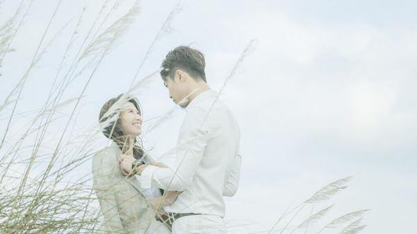 八里左岸往沙灘的路上有野生芒草間,新郎幫新娘披上他身上淺灰色的西裝,拍攝雲朵輕婚紗微電影