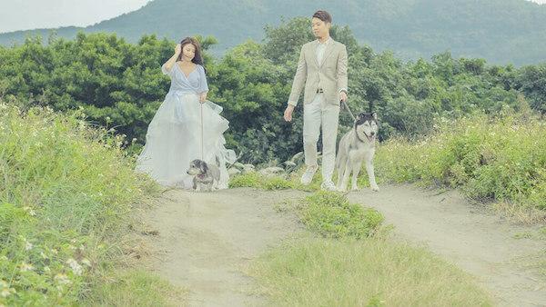 新人與愛犬在八里左岸往沙灘的路上漫步,海邊的風很大,正在拍攝雲朵輕婚紗微電影