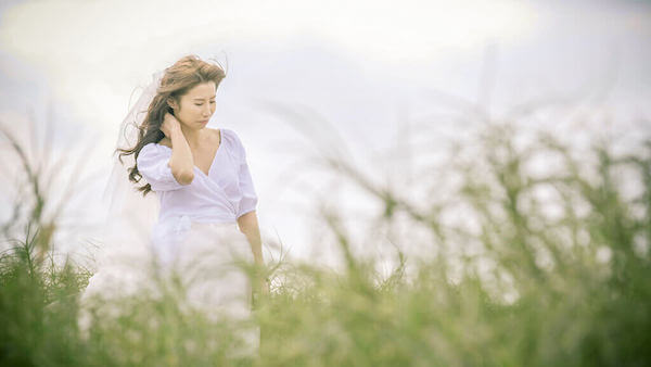 新娘單獨一人在八里左岸往沙灘的路上的野生芒草間擺POSE,拍攝雲朵輕婚紗微電影