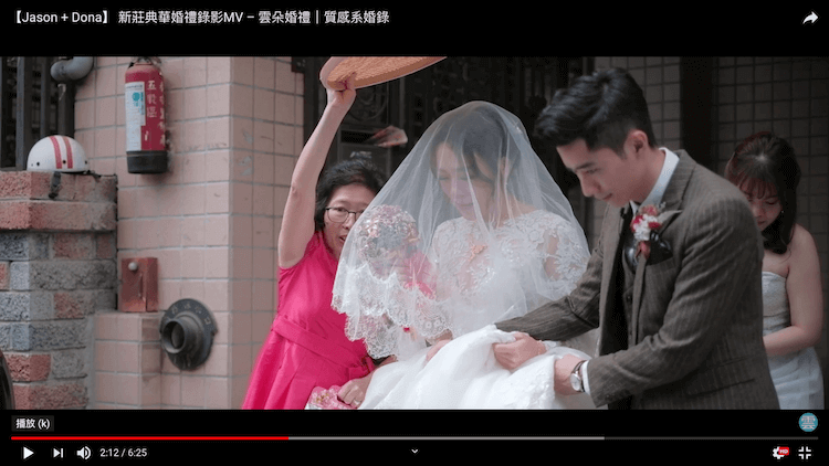 新娘穿白紗被新郎與媒人攙扶走出娘家大門口