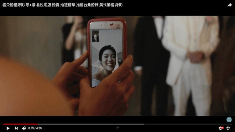 新娘透過手機看正在闖關遊戲的新郎