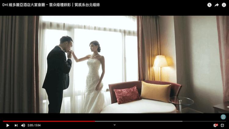 新郎親吻新娘手在維多麗亞酒店客房窗前