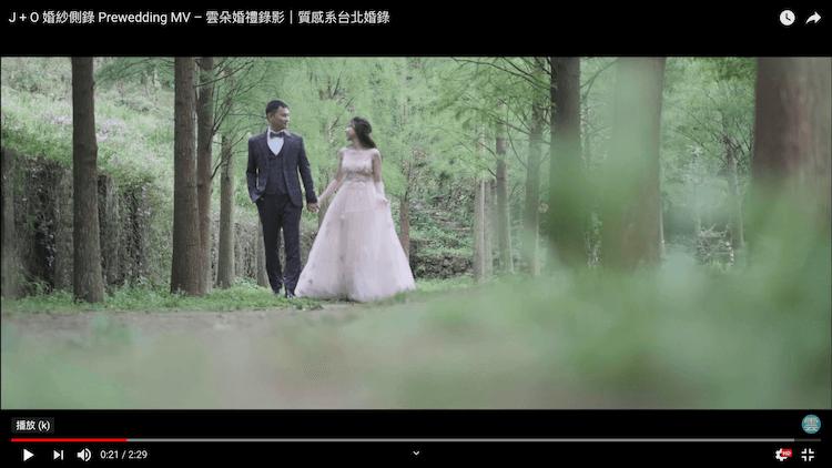 新人手牽手走在樹林間拍婚紗