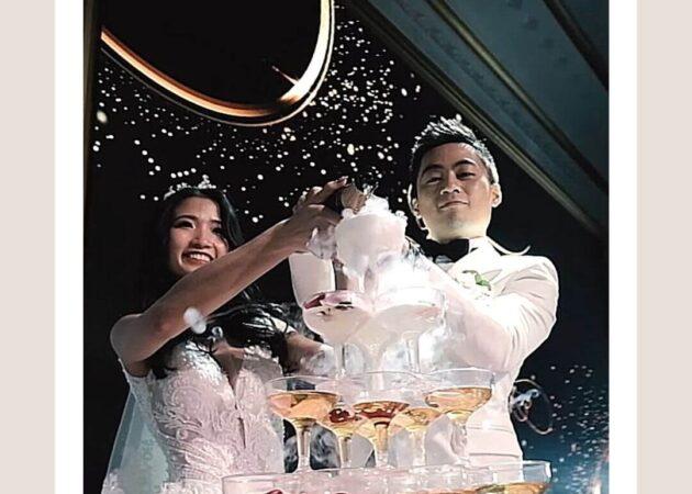 新郎跟新娘在舞台上倒著香檳酒