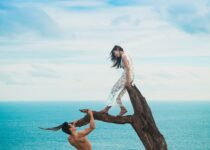 woman sitting on tree trunk with man holding on branch near sea under white clouds during daytime