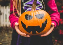selective focus photography of person holding pumpkin