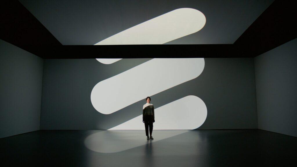 man in black jacket and black pants standing on white floor